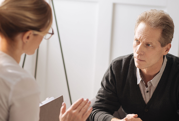 Doctor sat at hr desk with a patient estimating the risk of suicide