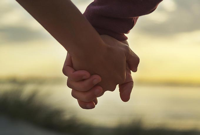 Couple in a positive relationship, walking holding hands on the beach