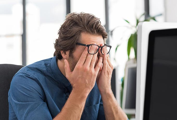 Man struggling to cope at work - take a mental health day