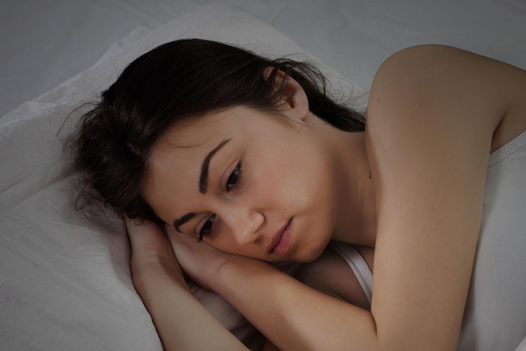 Women laying awake in bed