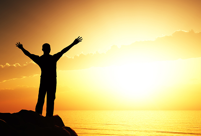 Man standing with his arms wide welcoming the sunrise