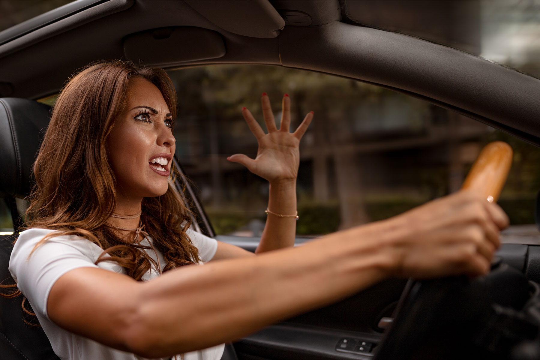 A woman driving, getting angry