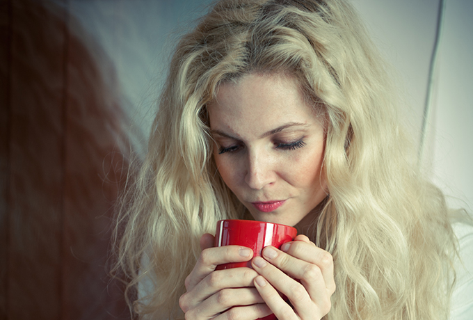 sad struggling woman drinking a cup of tea
